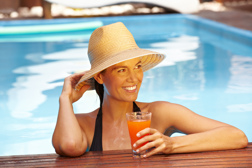 Woman in a swimming pool protecting her skin from sun damage with a broad rimmed hat.
