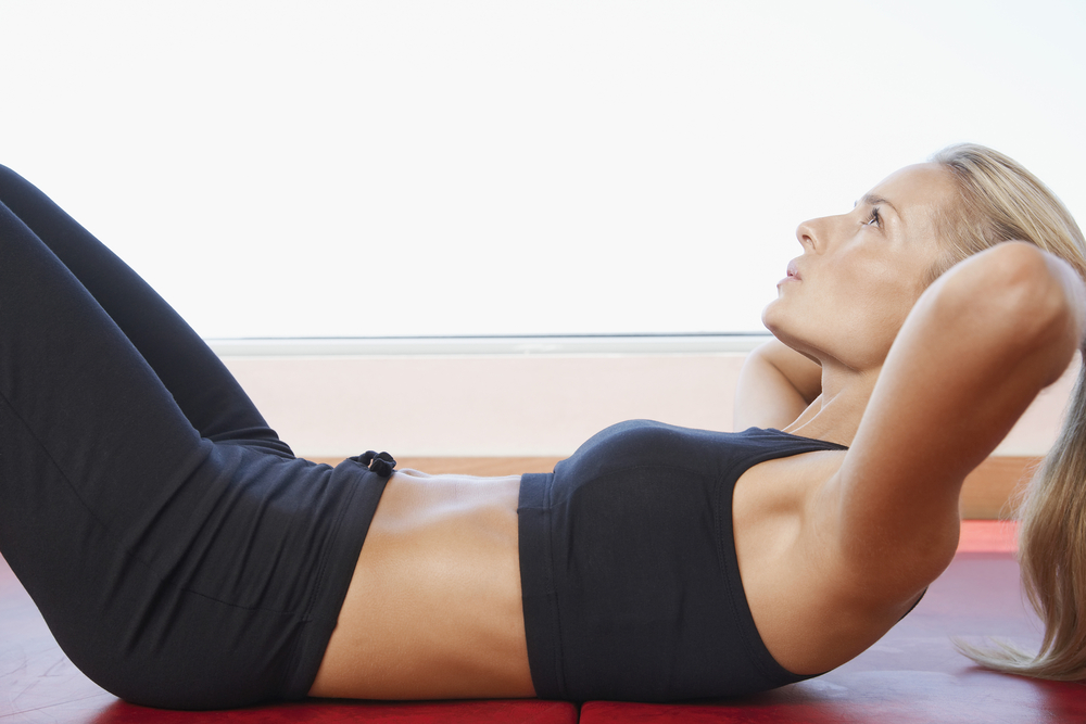 Woman toning her abs by exercising in the gym.
