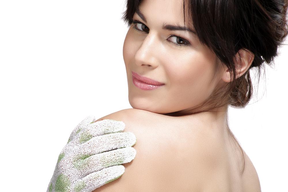 Woman exfoliating her skin with a scrub.