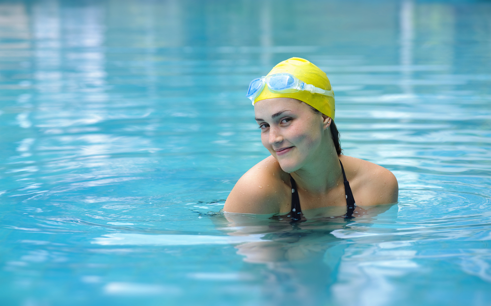 Beautiful woman with a swimming cap posing in a swimming pool.