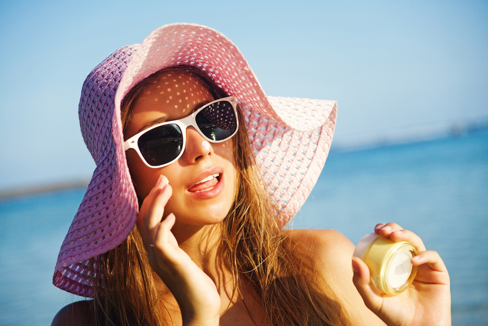 Woman wearing sunglasses and a hat applying sunscreen on a beach in Bali.