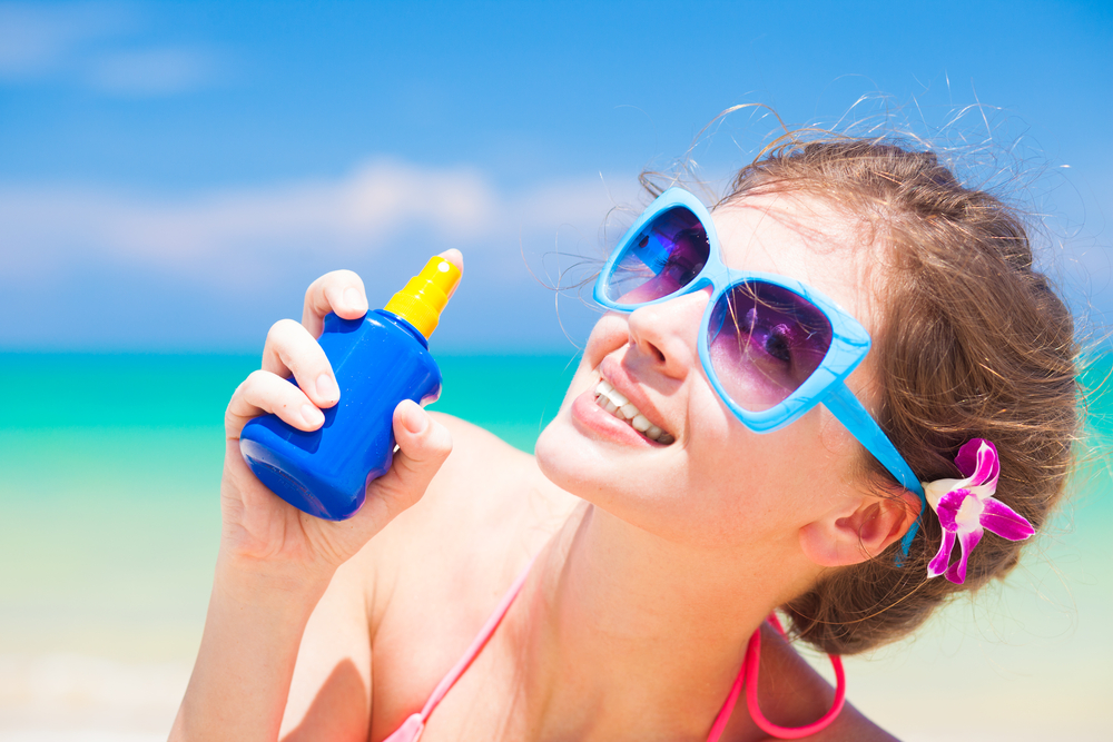 Woman holding a bottle of sunscreen