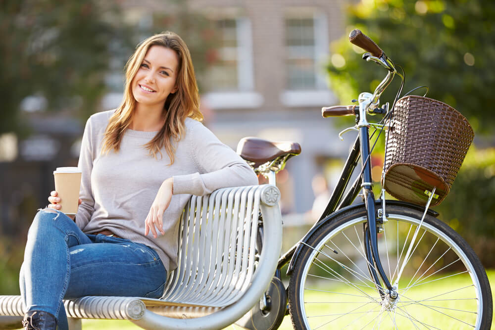 Smiling woman at park bench next to bicycle