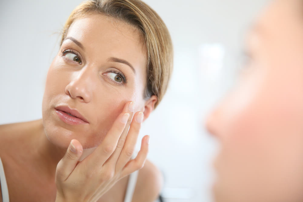 Woman applying cream in front of mirror