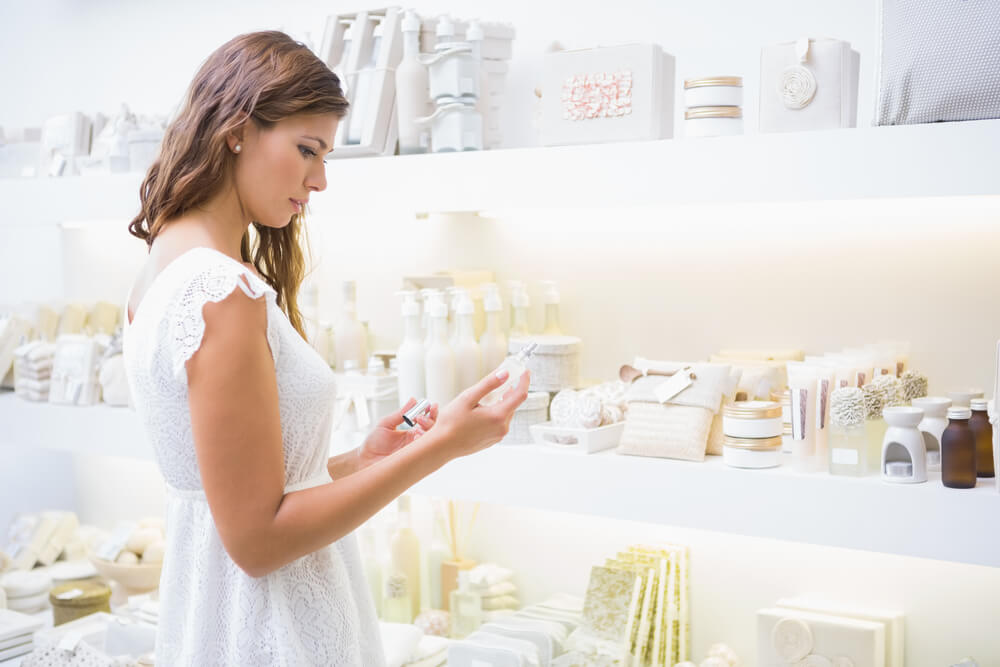 Woman in cosmetics store reading ingredients list of product