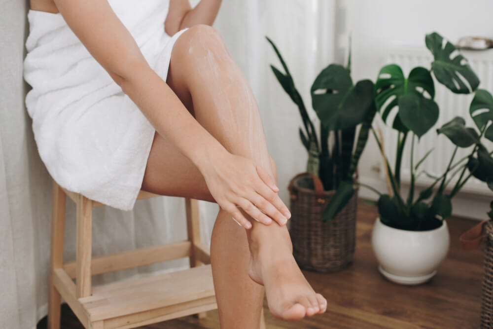 Woman applying leg cream