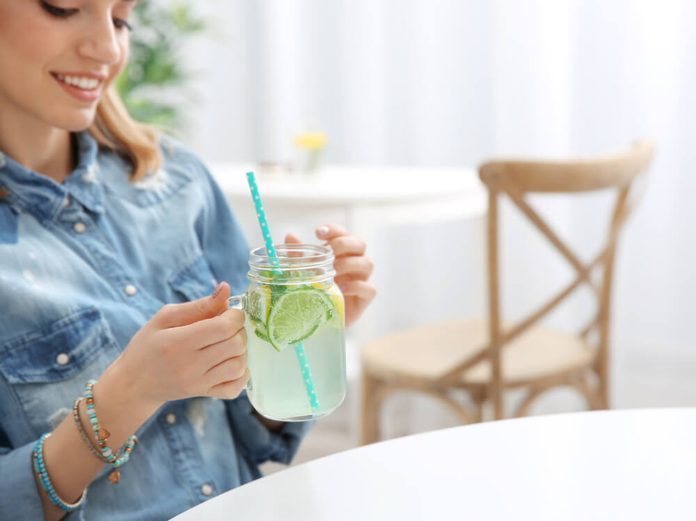 Woman drinking lime infused water