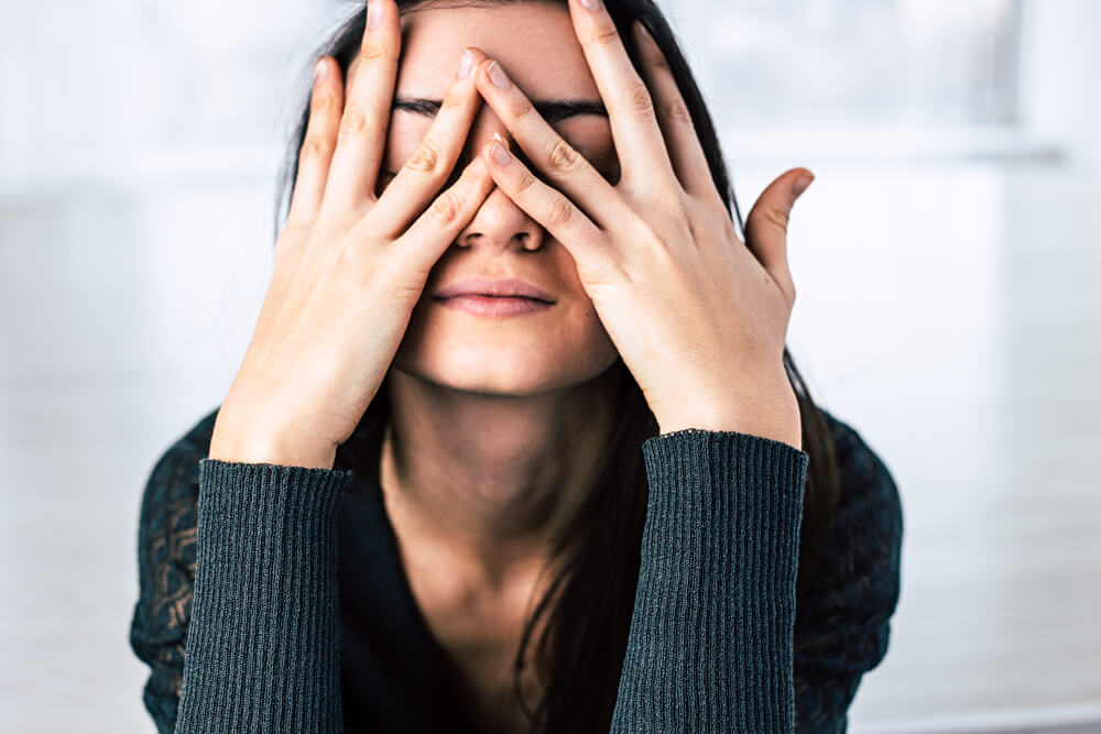 Stressed woman with hands in front of face