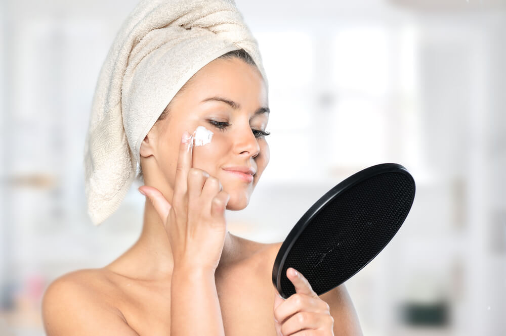 Woman holding mirror applying face cream