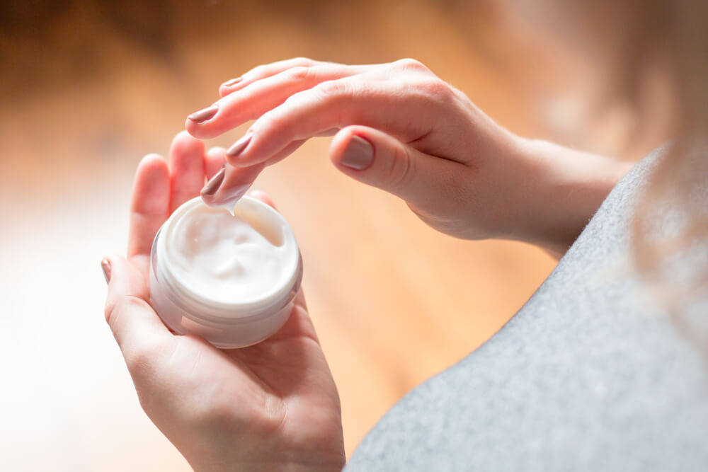 Woman dipping fingers into skin cream