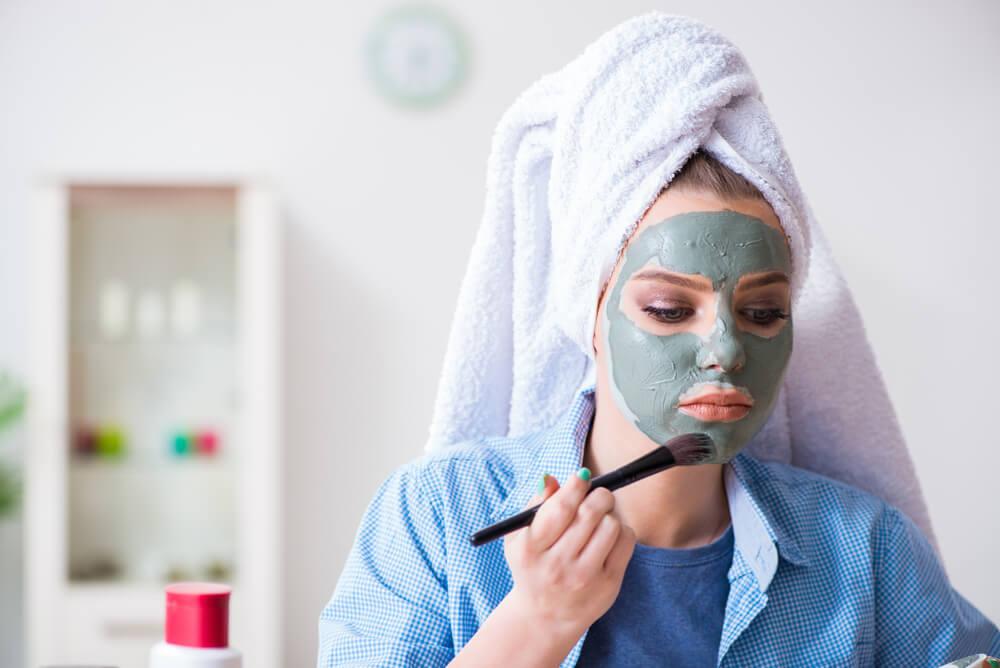 Woman applying facial mask to skin
