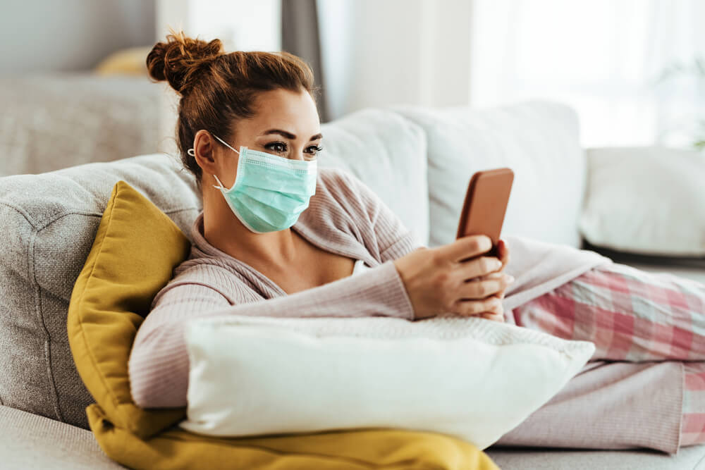 Woman on sofa wearing face mask