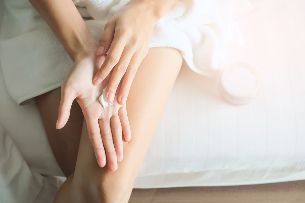 Woman applying cream on hands on bed