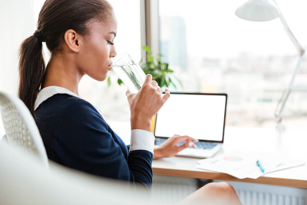 Woman at desk drinking glass of water