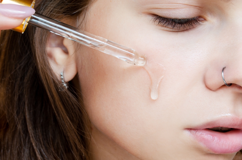 Woman using dropper to apply serum directly to face