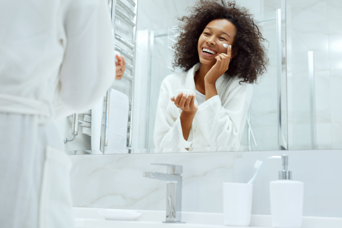 Woman looking in mirror applying face cream