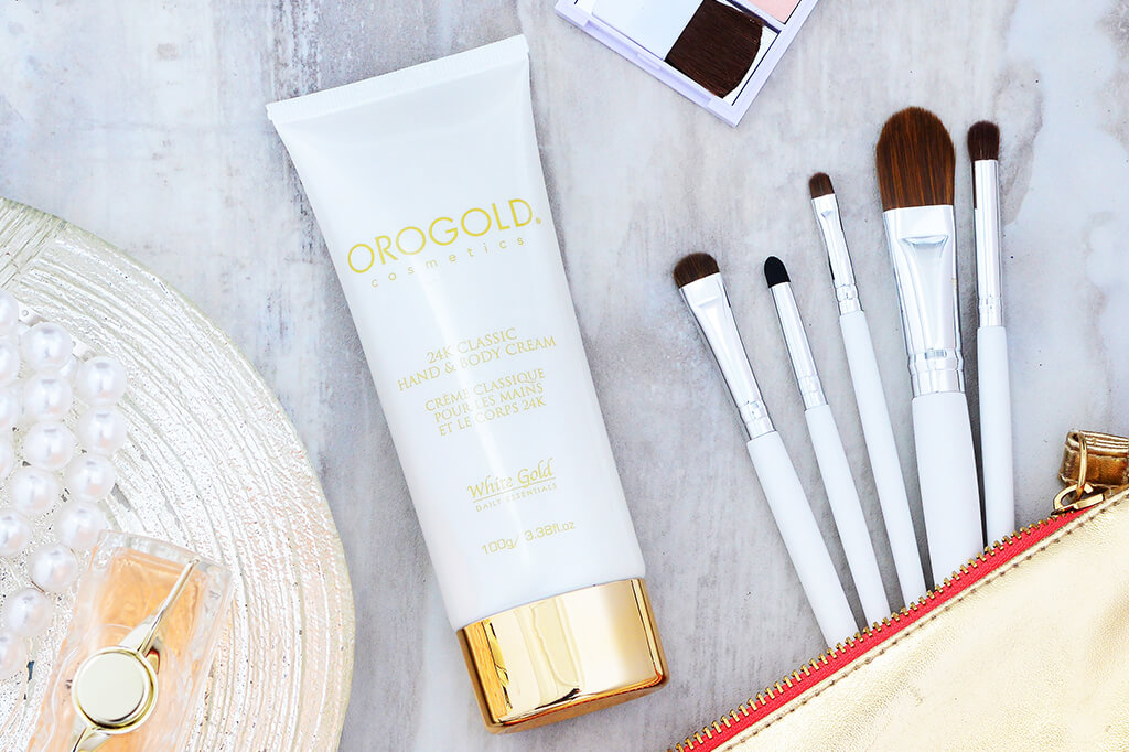 The OROGOLD 24K Classic Hand and Body Cream on table with makeup and makeup brushes