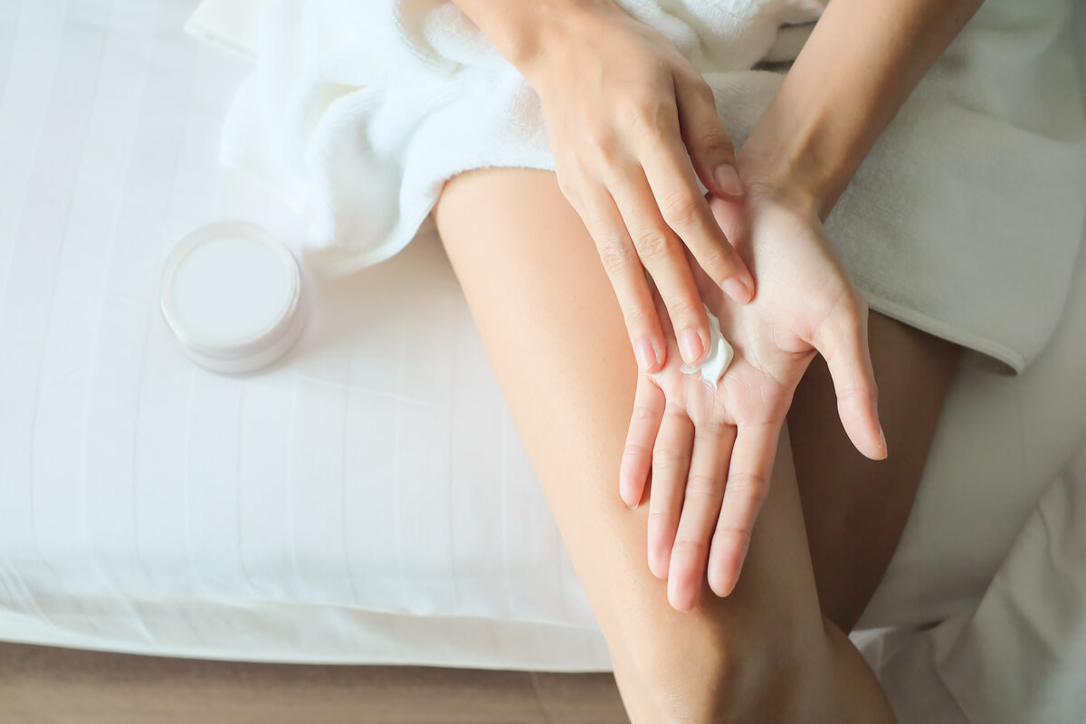 Woman applying cream on hands