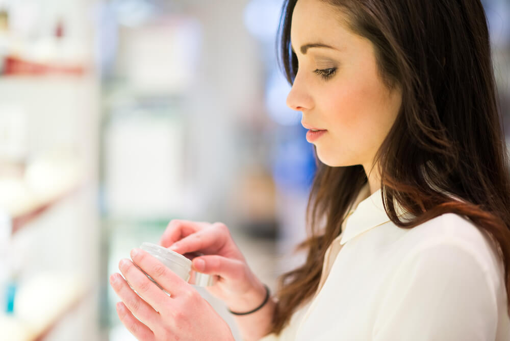 Woman sampling skin cream at store