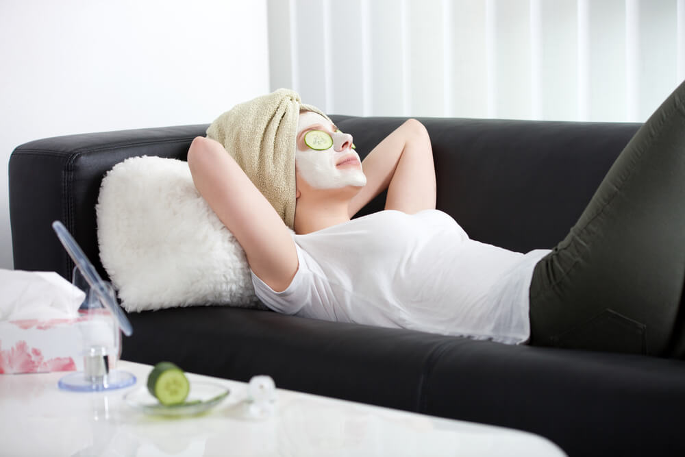 Woman on sofa with face mask on