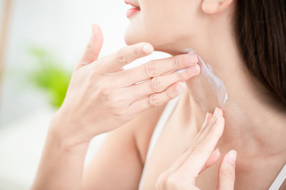 Woman applying neck cream