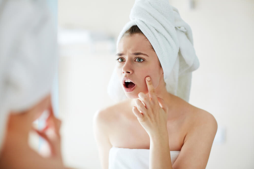 Woman looking at face in mirror in shock