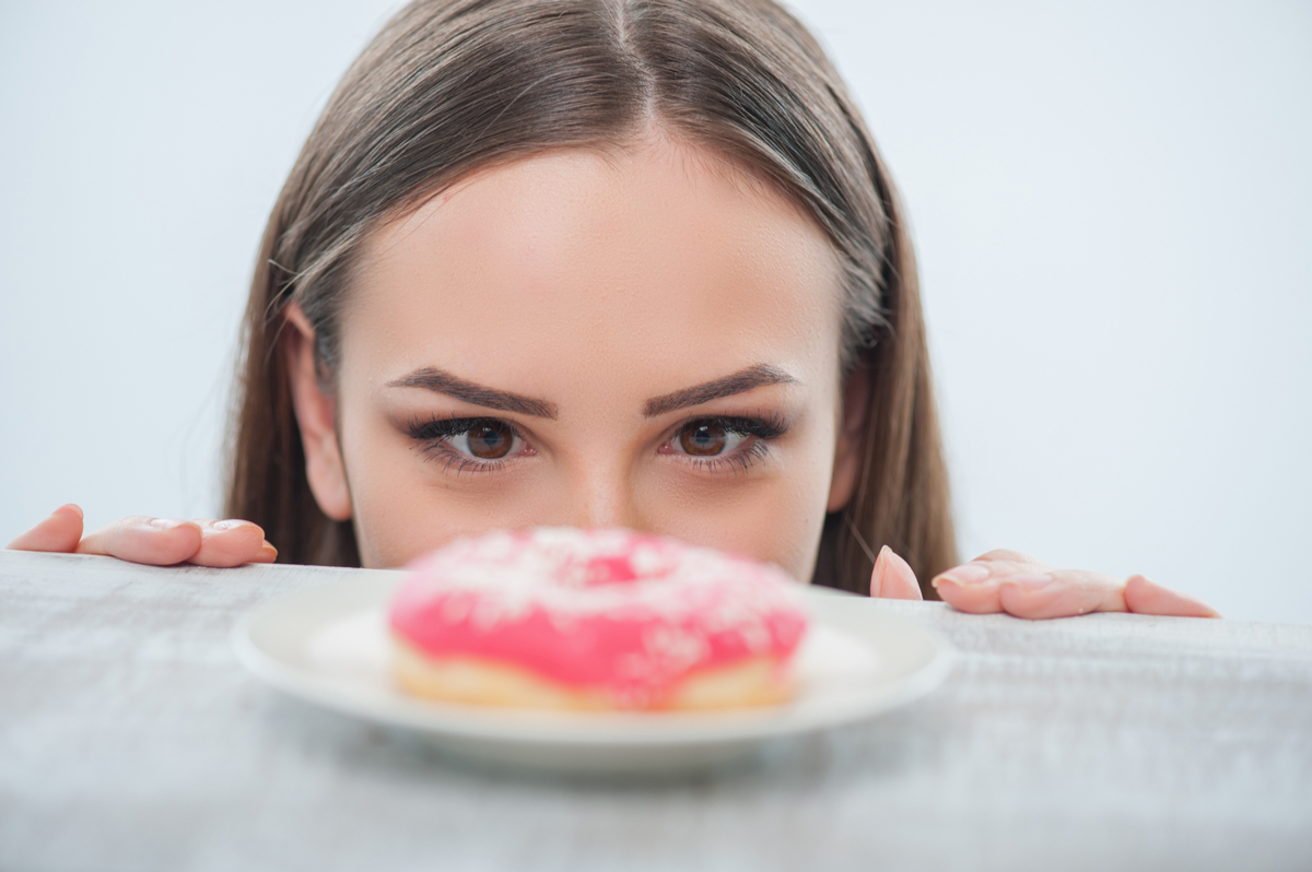 Woman looking at donut on plate