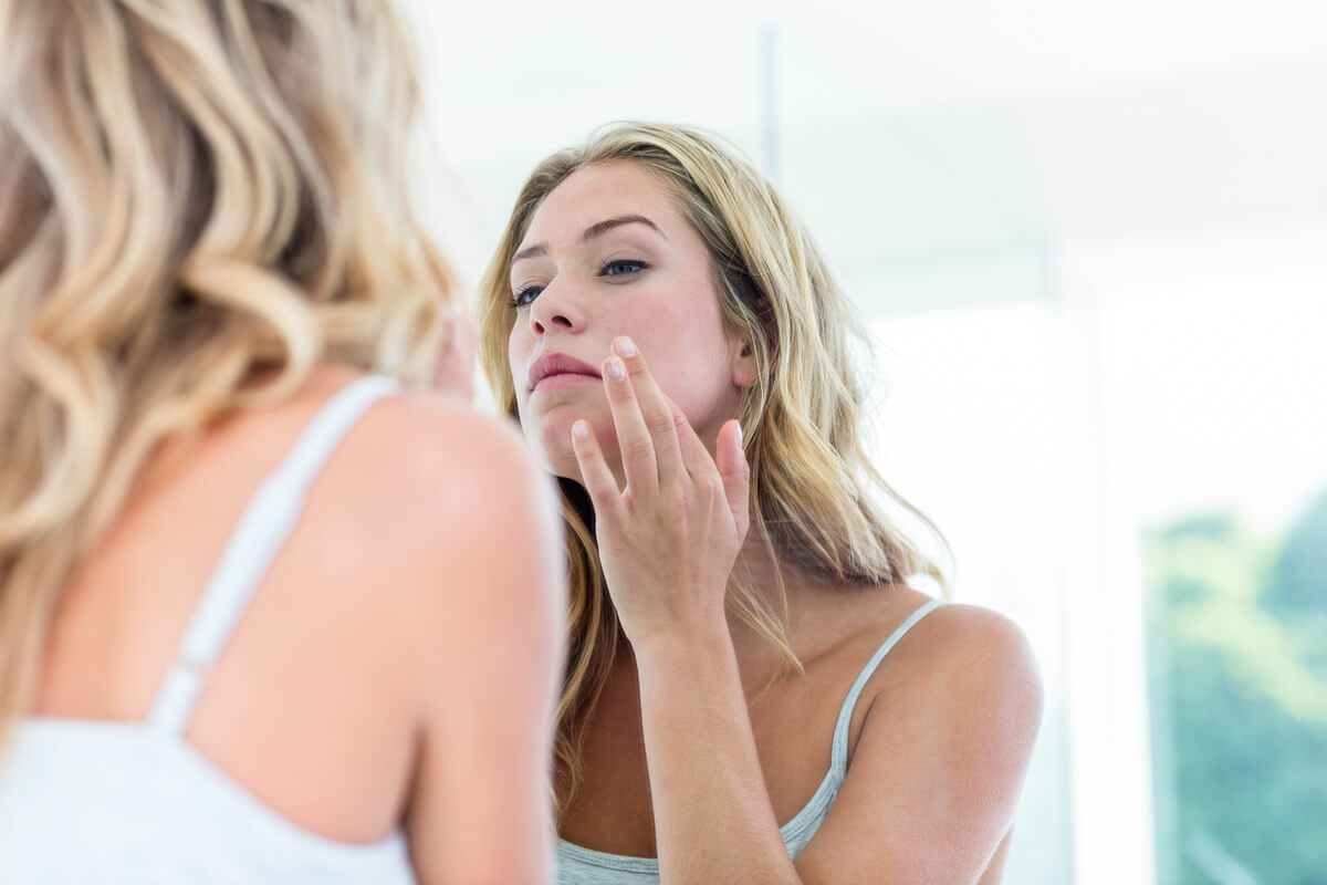 Woman looking at face skin in mirror