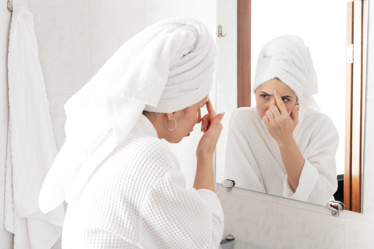 Woman looking at frown lines in mirror