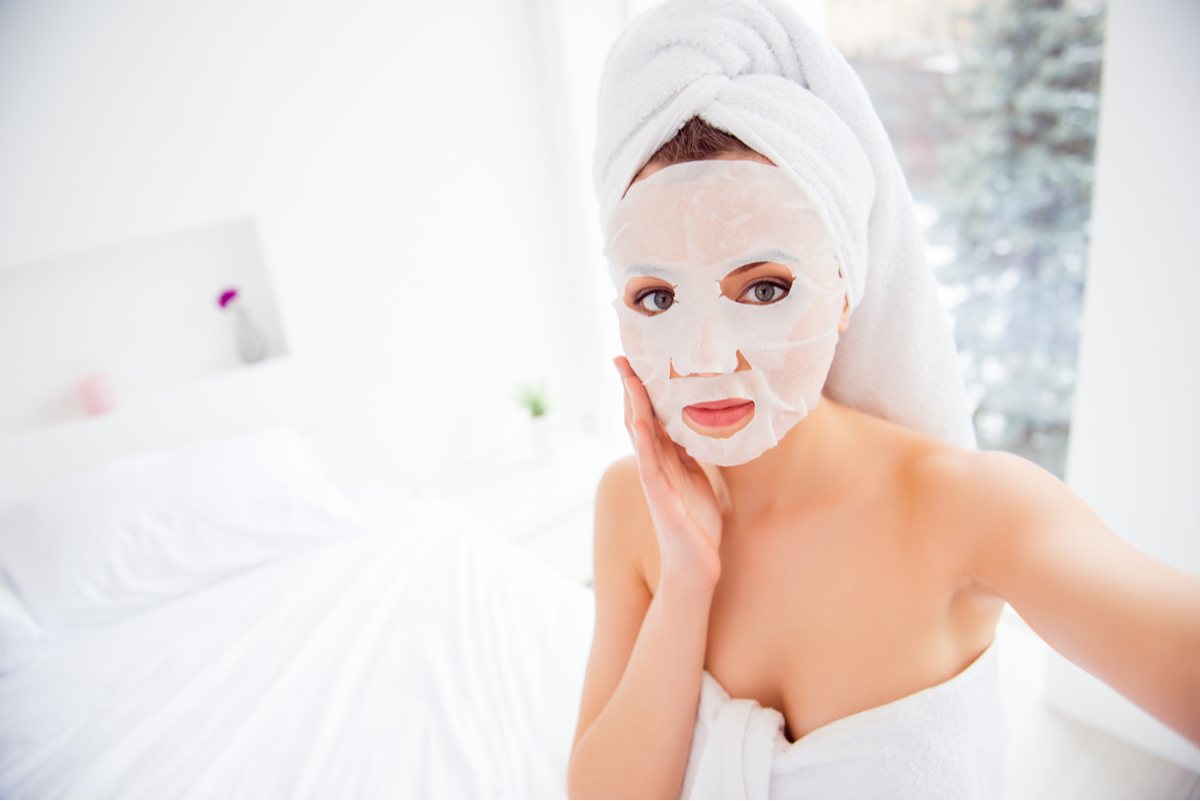 Woman in bathroom with sheet mask on face