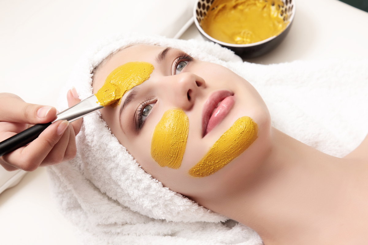 Woman at spa having face mask applied