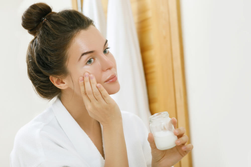 Woman applying coconut oil in mirror
