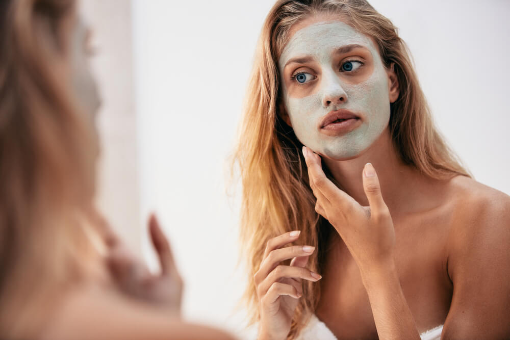 Woman with face mask looking in mirror