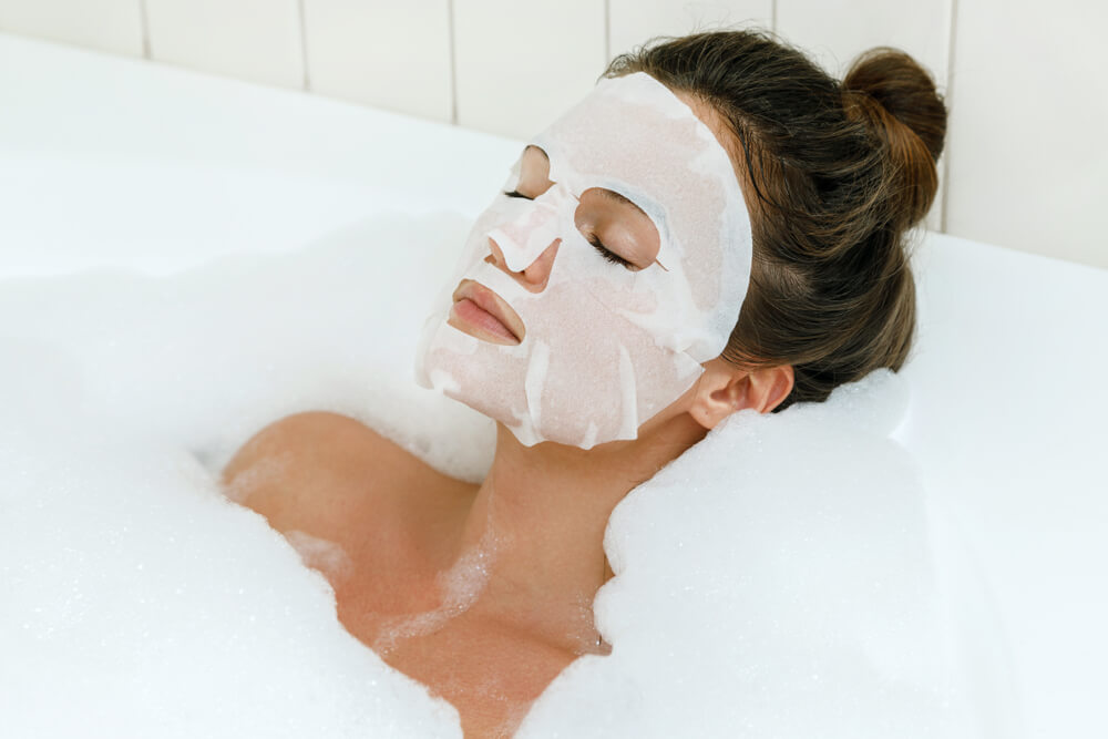 Woman with sheet mask in bath