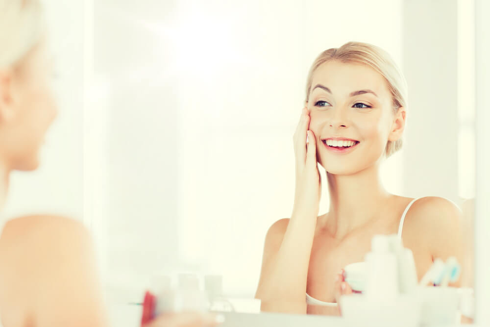 Woman touching skin looking in mirror