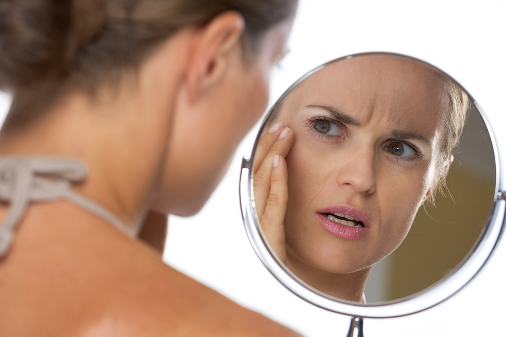 OROGOLD - Young woman concernedly looking in the mirror