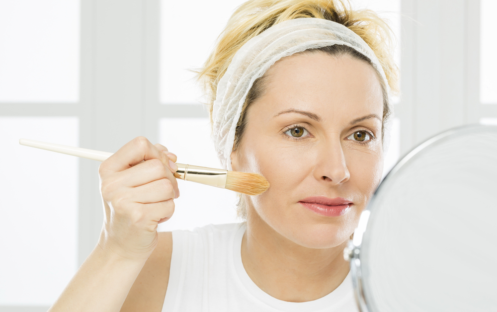 Forty plus woman applying foundation makeup.