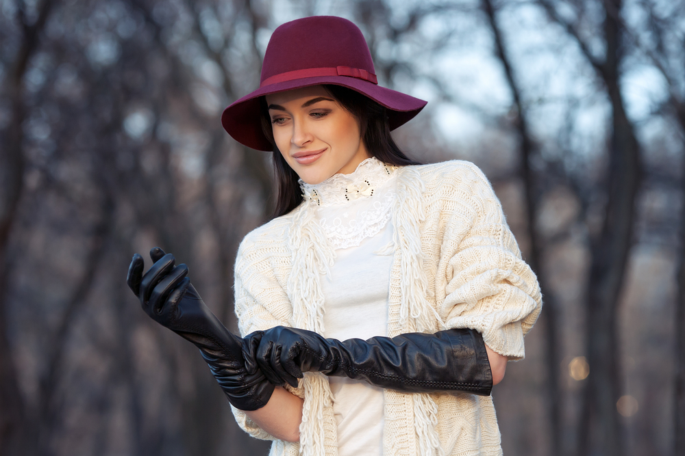 Fashionable woman in a white dress wearing gloves to protect her hand from the winter chill.