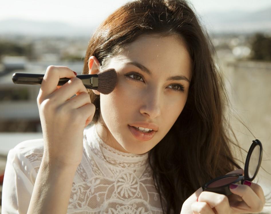 Woman applying blush on her cheeks.