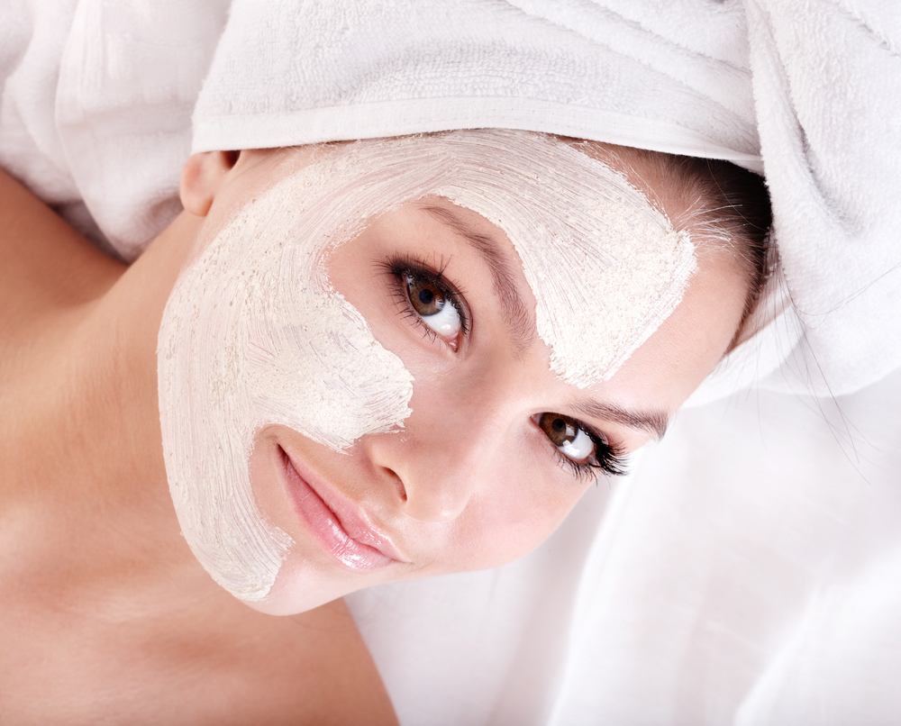 happy woman with a luxurious face mask in a spa.