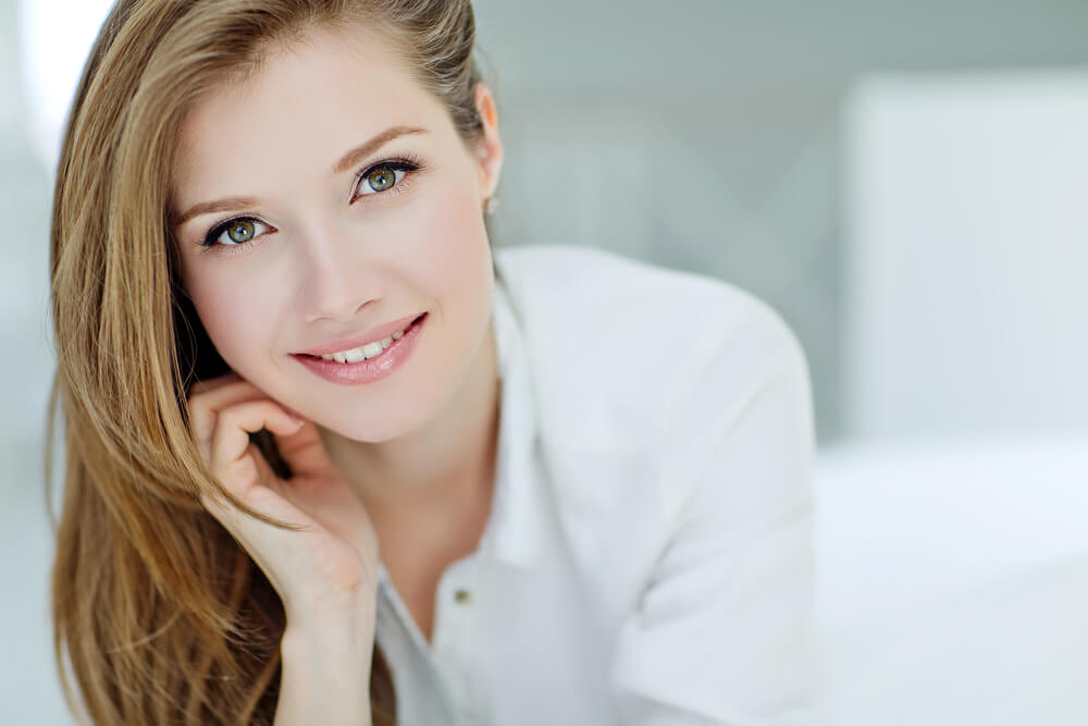 Smiling woman in white with chin resting on hand