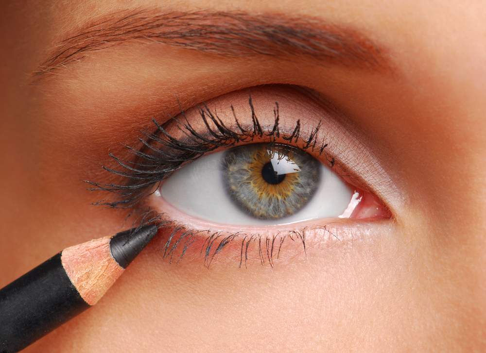 Woman applying a pencil eyeliner.