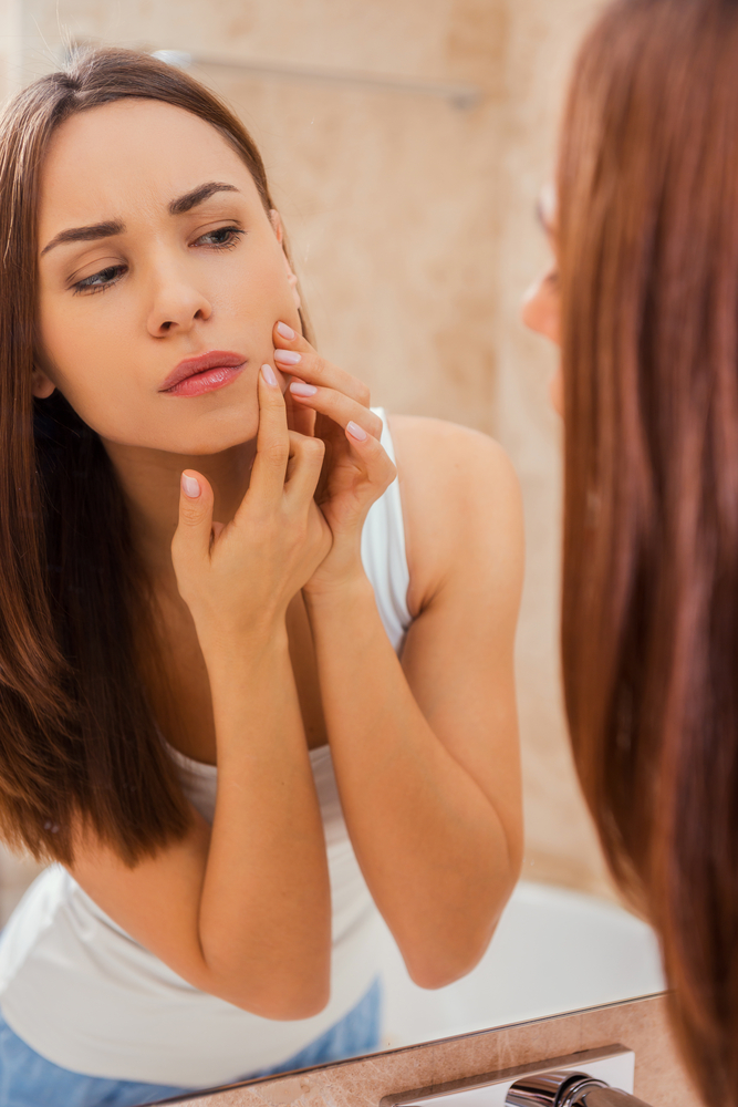 Woman looking at her zit in the mirror.