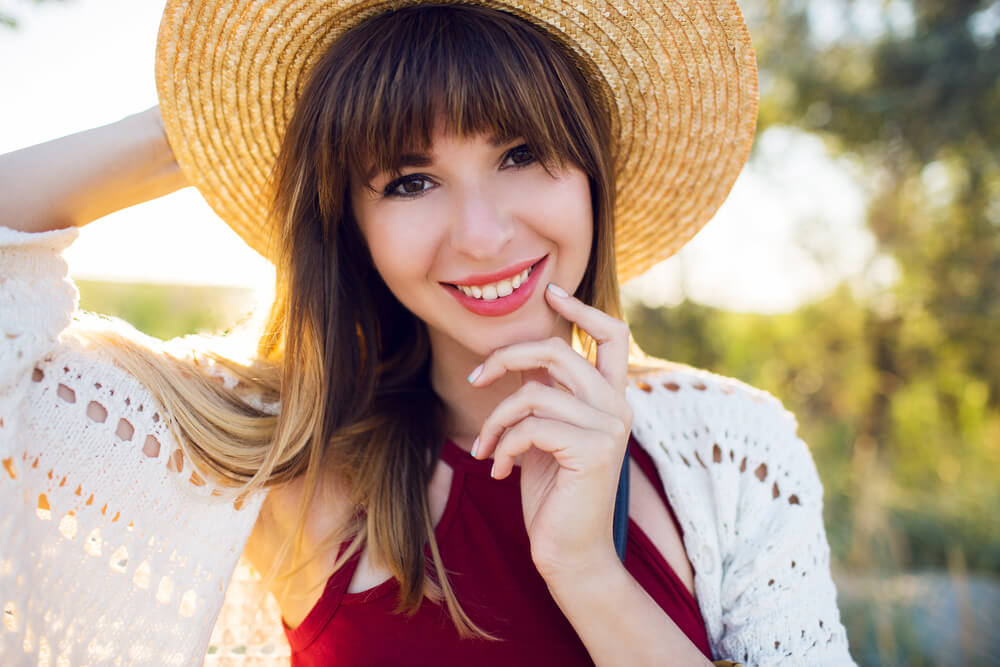 Smiling woman with bangs and a hat