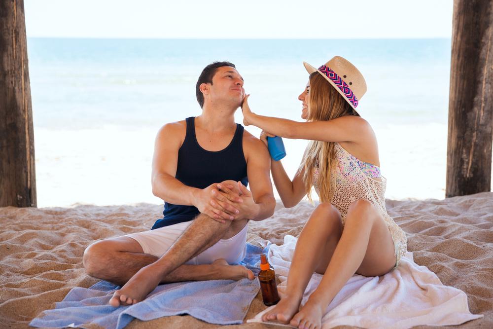 Couple applying sunscreen