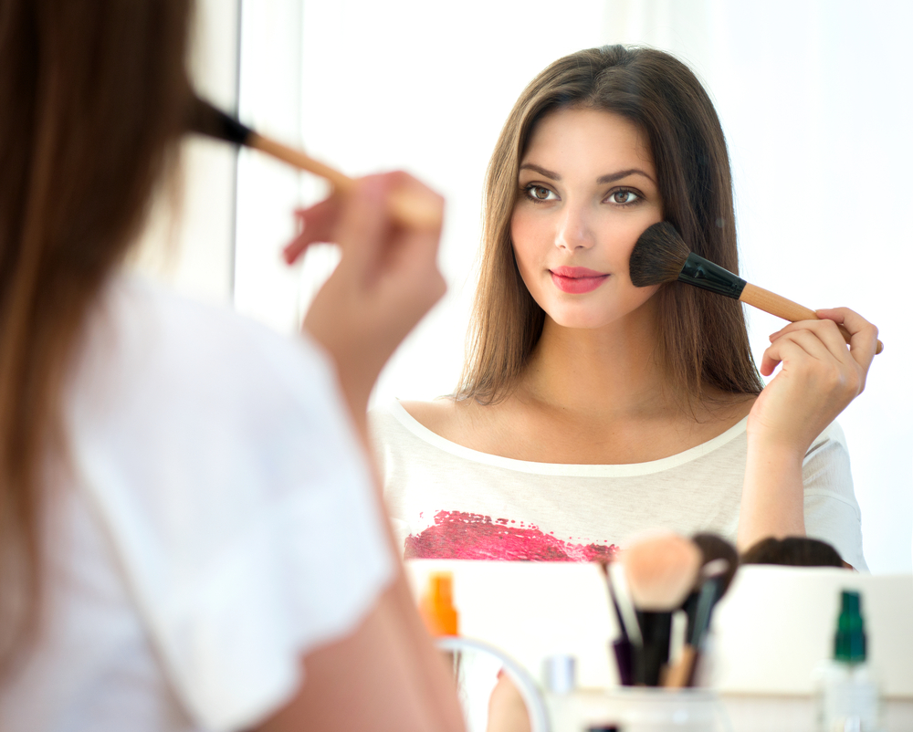 Woman looking into the mirror and applying blush.
