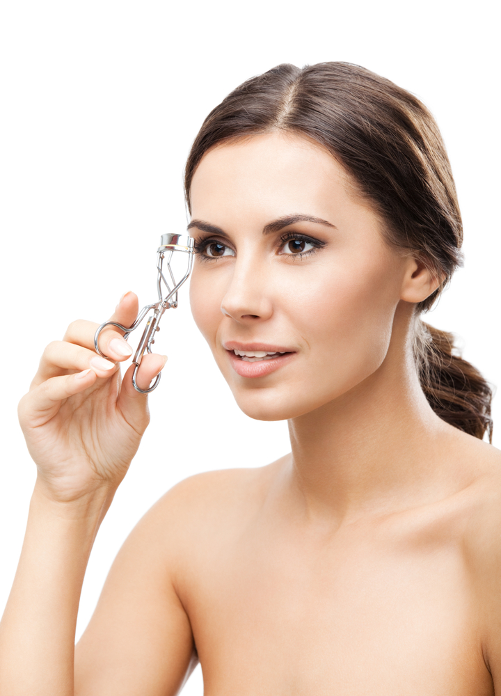 Woman curling her lashes with a lash curler.