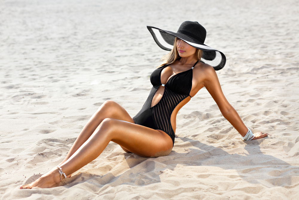 Fashionable woman with a beautiful tan in a beach.