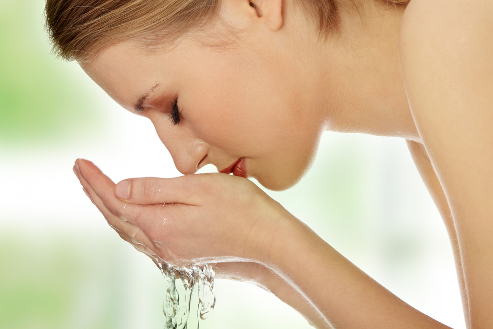 Woman washing her face.