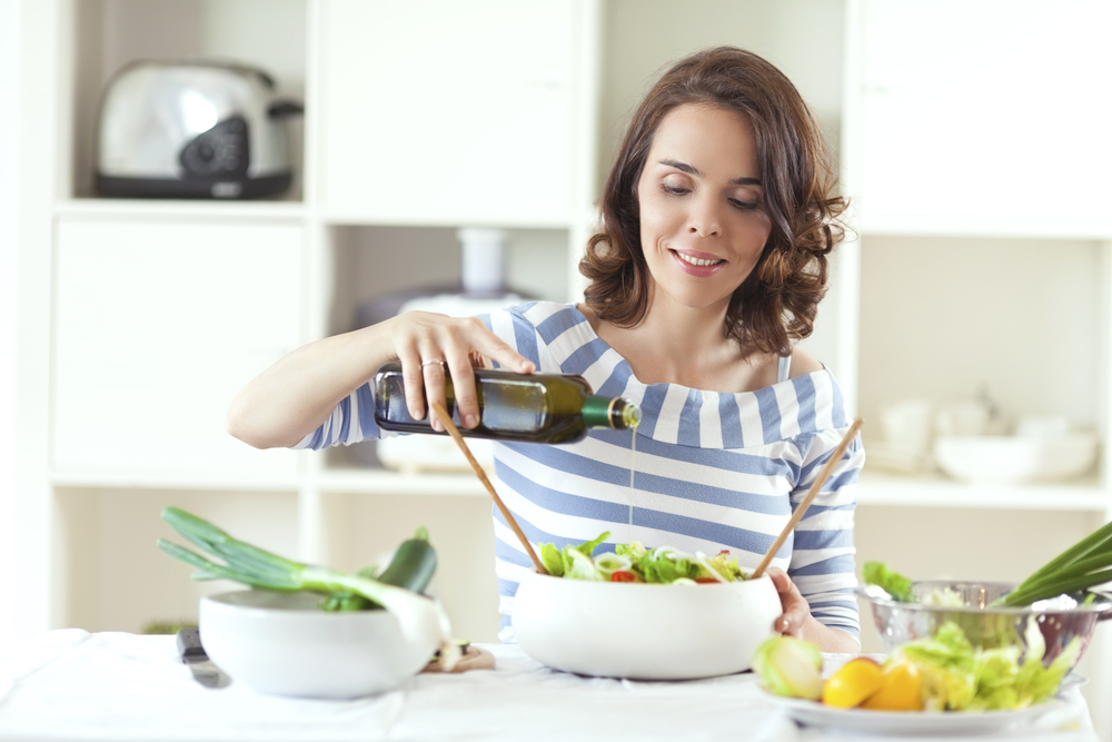 Woman pouring olive oil in her salad.